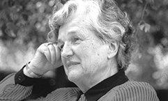 Elisabeth Belling sitzt entspannt im Grünen und blickt freundlich zur Seite.