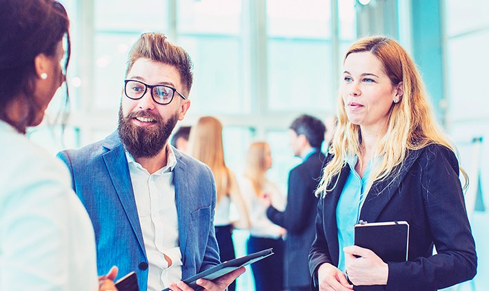 Drei jüngere Menschen im Businessdress stehen nebeneinander und sprechen angeregt und freundlich miteinander.