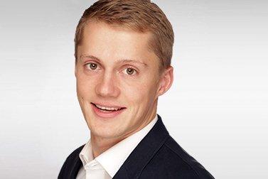Christian Feise ist Alumni-Stipendiat für ein Masterstudium und schaut lachend in die Kamera.