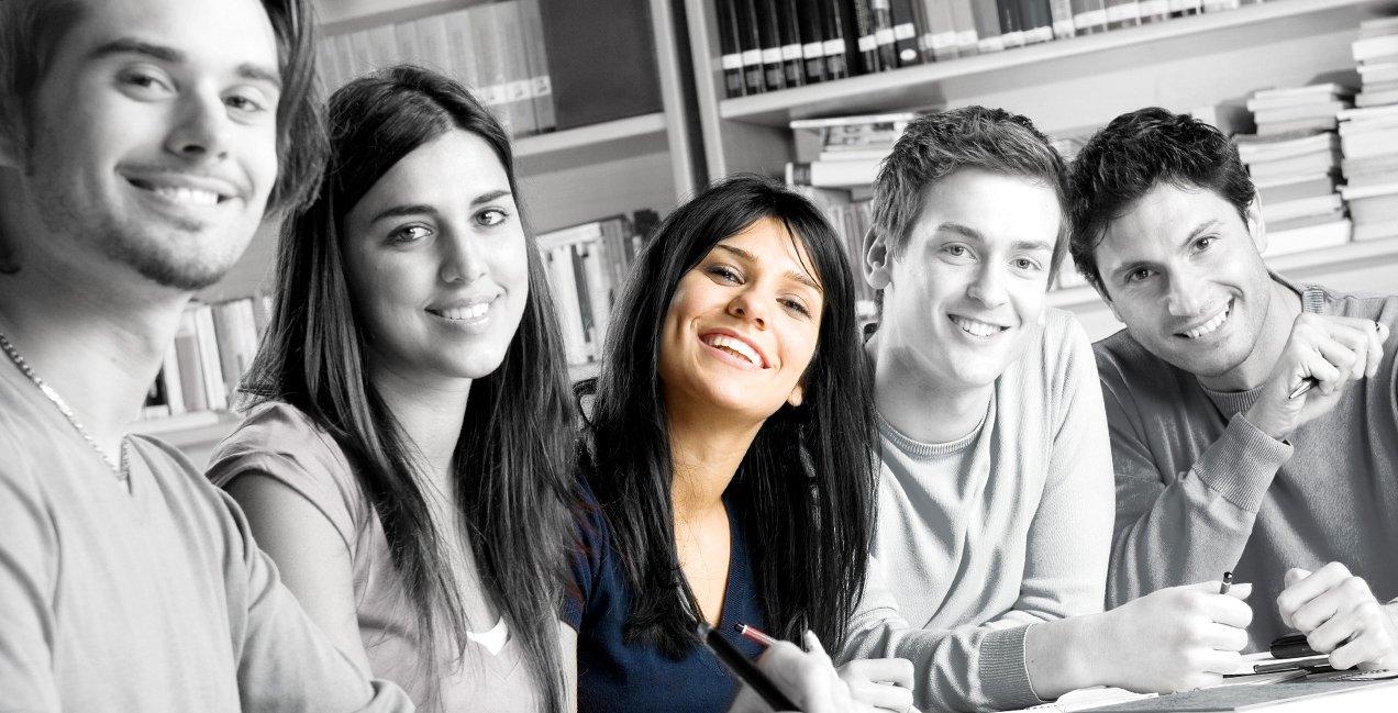 Fünf junge Studenten sitzen an einem Tisch und strahlen lachend in die Kamera.