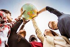 Mehrere junge Menschen im Ausslandssemester werden von unten fotografiert und halten gemeinsam einen Globus in der Hand.