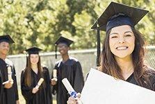Vier junge Absolventen in ihrer Universitätsrobe blicken glücklich in die Kamera, während die vordere Frau ein Zertifikat ihrer Promotion in der Hand hält.