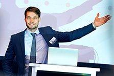 Ein selbstbewusster junger Mann im Anzug steht auf einer Bühne und präsentiert einladend seine Habilitation.