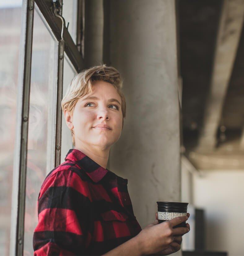 Eine junge Frau steht an einem Fenster, hält einen Kaffee in der Hand und blickt positiv nach vorne.